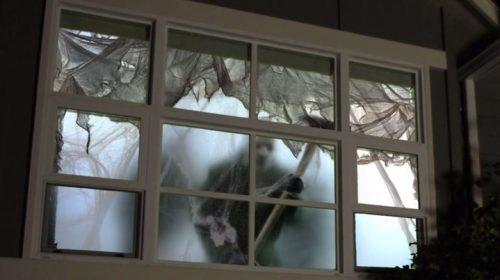 AtmosFX projecting an axe murderer onto a window for Halloween