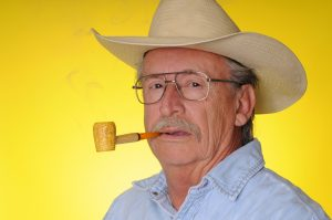 A reckless old man smokes his corncob pipe before bed.