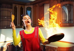A woman, trying to cook, is terrified by a pan fire.